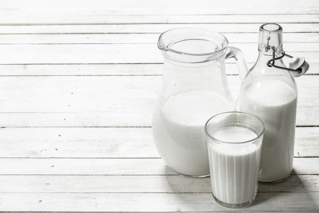 白い木製のテーブルの上の水差しの新鮮な牛乳。