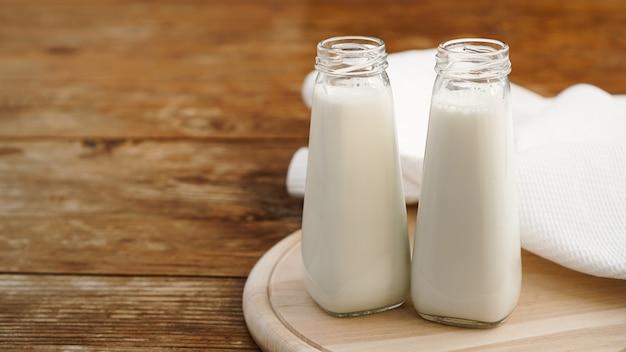 두 개의 유리 병에 신선한 우유. 목재 소박한 표면. 건강한 식생활