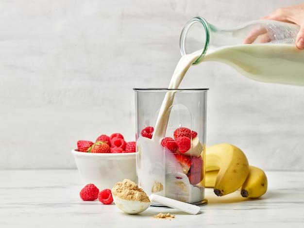 건강한 아침 식사 밀크셰이크를 만들기 위해 블렌더 용기에 신선한 우유를 붓는다