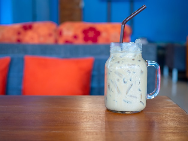 Fresh milk tea in a glass placed on a wooden floor. with free space