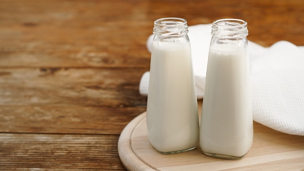 Fresh milk in two glass bottles. wood rustic surface. healthy eating