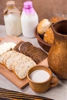 Свежее молоко, цельнозерновой хлеб и сыр, аккуратно поданные на деревянной разделочной доске, станут здоровой закуской в деревенском стиле.