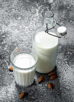 素朴なテーブルにアーモンドと新鮮な牛乳。