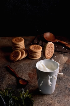 Fresh milk with homemade cookies on a wooden table, dark background.