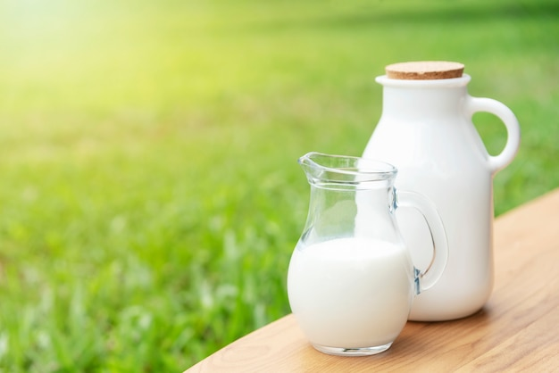 Fresh milk on wood table with green nature background.