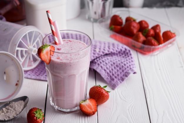 Fresh milkshake with strawberries on a light table.