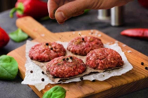 향신료 바다 소금을 붓는 손으로 신선한 다진 고기 공 음식 사진 요리 과정