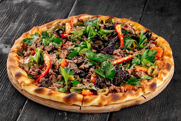 Fresh minced meat pizza with hot pepper and greens