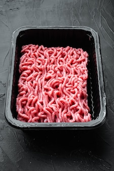 Fresh minced meat in plastic box packaging tray, on black