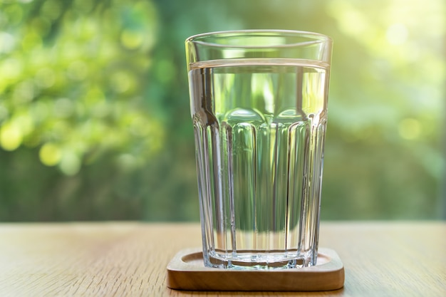 Fresh mineral drinking water in a glass on wooden table and natural blurred scene.