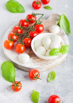Fresh mini mozzarella cheese on vintage chopping board with tomatoes and basil leaf on stone kitchen background.