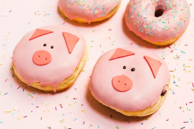 ピンクの背景の上にクリームで艶をかけられた新鮮なミニ豚ドーナツ