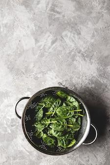 오래 된 콘크리트 테이블에 소 쿠 리에 신선한 미니 시금치. 건강 식품, 친환경 제품. 비건