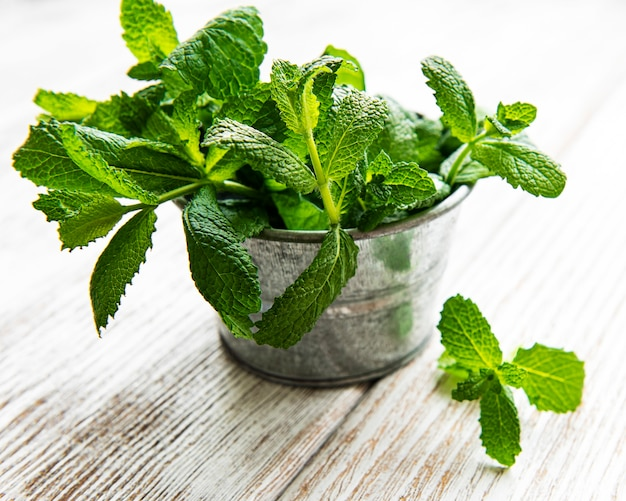 Fresh mint in bucket on a white woodwn table