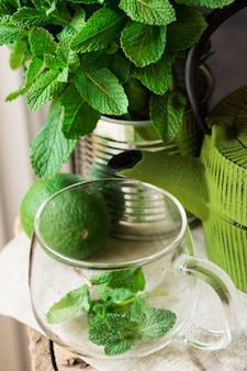 Fresh mint bunch in tin can, glass cup, pot, lime on linen cloth