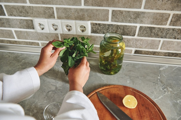 キッチンの木製ボードにレモンとナイフのスライスの背景に認識できない女性の手に新鮮なミントの葉