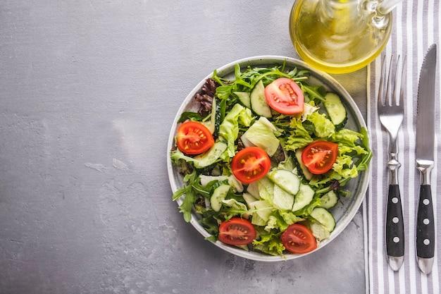 Свежий микс салатов с овощами на тарелке вид сверху