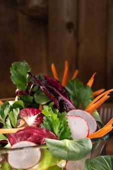 素朴な茶色の木製テーブルにオリーブオイルドレッシングとフレッシュミックス野菜サラダ