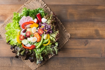 Fresh mix vegetation salad on brown wood background
