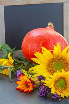 Fresh mixed autumn flowers with raw pumpkin and blackboard