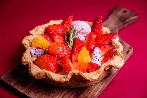 Fresh mixed fruit tart on red background