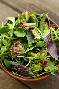Свежий смешанный зеленый салат в миске на деревянном столе крупным планом