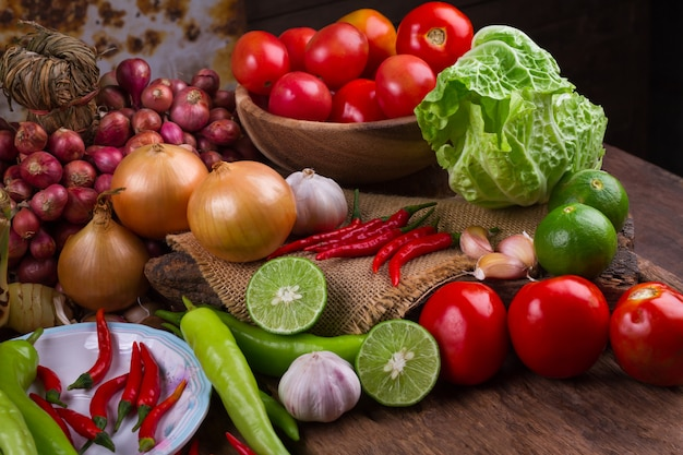 Fresh mixed organic vegetables in bamboo basket on old wood table background