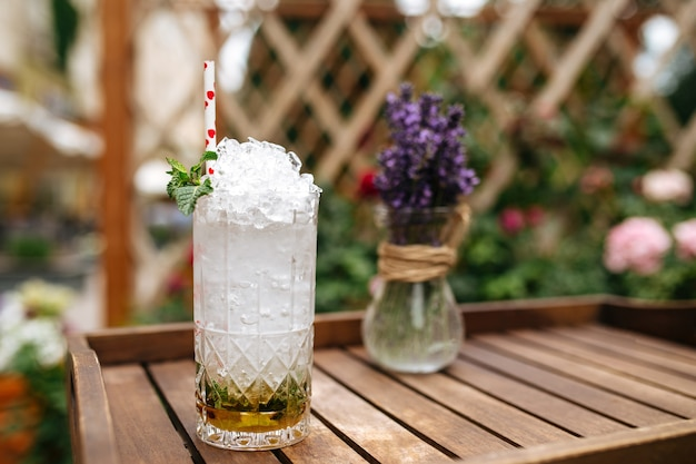Свежий коктейль мохито с колотым льдом на деревянном подносе