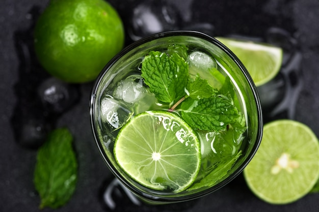 Fresh mojito cocktail with fresh lime and mint leaf on black stone background