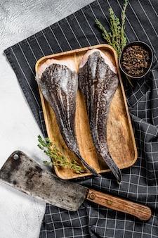 식 칼으로 나무 쟁반에 머리없는 신선한 monkfish. 회색 배경. 평면도