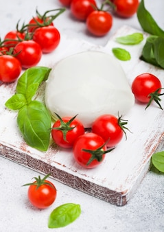 Fresh mozzarella cheese on vintage chopping board with tomatoes and basil leaf on stone kitchen.