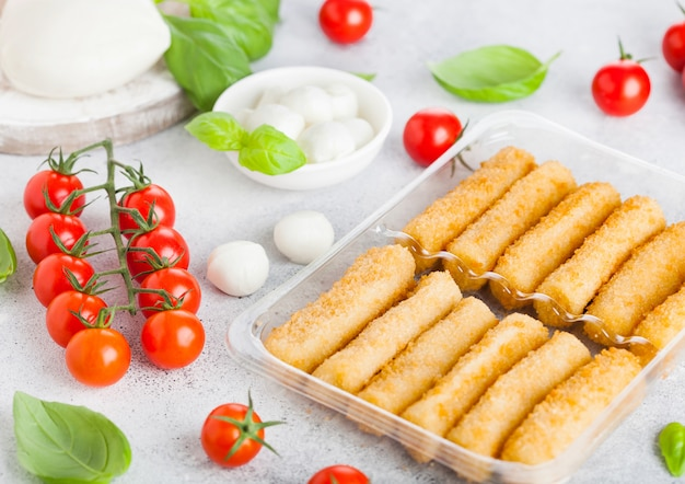 Fresh mozzarella cheese on vintage chopping board with tomatoes and basil leaf and tray with cheese sticks on stone kitchen.