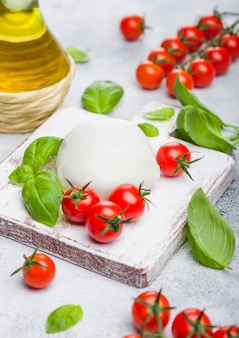 Fresh mozzarella cheese on vintage chopping board with tomatoes and basil leaf with olive oil on stone kitchen.