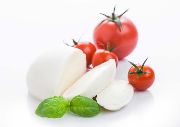 Fresh mozzarella cheese with tomatoes and basil leaf with reflection