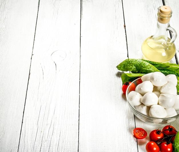 Свежая моцарелла с оливковым маслом, помидорами и зеленью на белом деревянном фоне