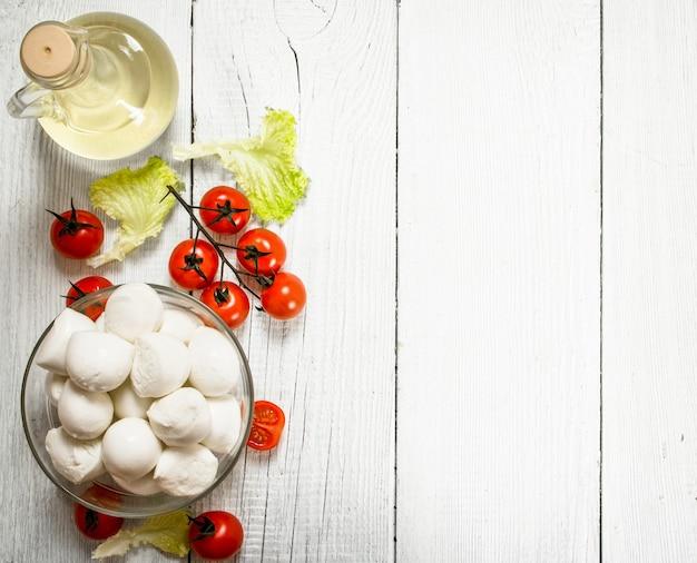 Свежая моцарелла с оливковым маслом, помидорами и зеленью.
