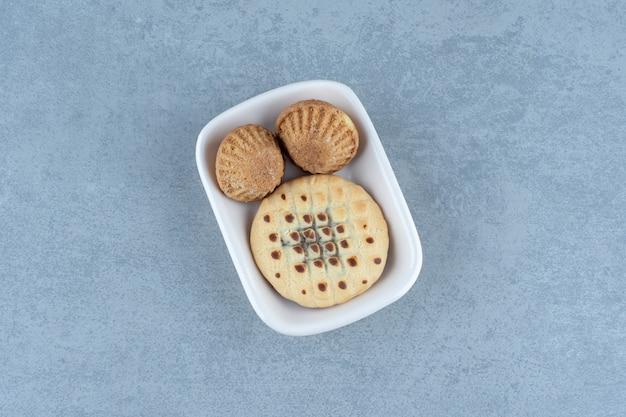 白いボウルにクッキーと新鮮なマフィン。