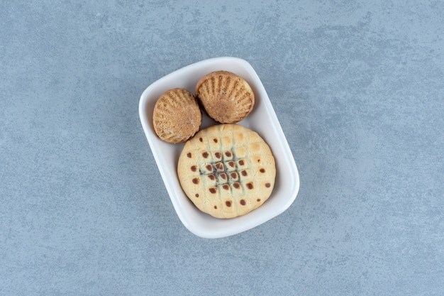 Muffin freschi con biscotto in ciotola bianca.