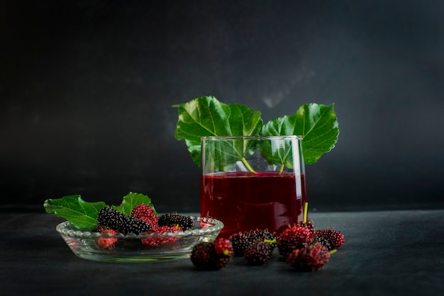 Fresh mulberry fruit in a bowl and juice in a glass