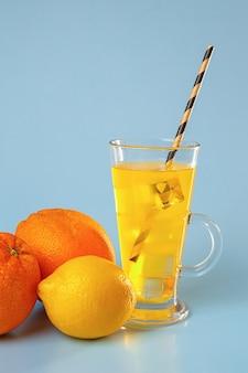 유리에 얼음과 신선한 multifruit 주스. 오렌지와 레몬 푸른 공간에