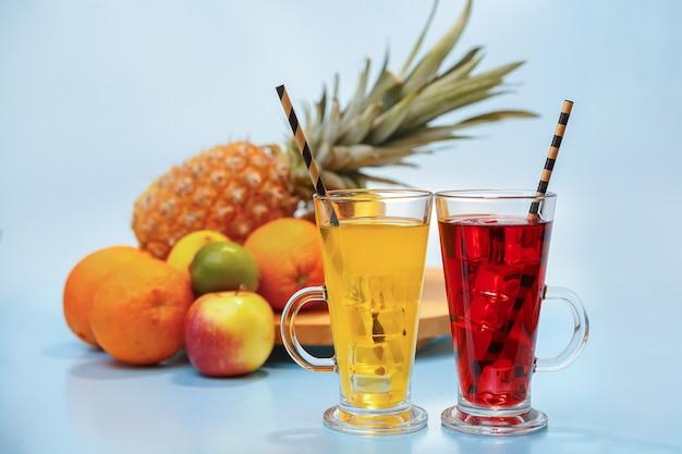 유리에 얼음과 신선한 multifruit 주스. 푸른 공간에 파인애플, 오렌지, 바나나, 레몬, 사과