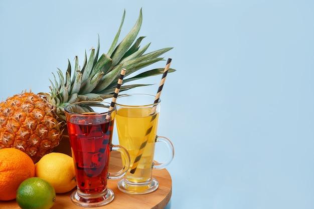 유리에 얼음과 신선한 multifruit 주스. 파란색 테이블에 파인애플, 오렌지, 바나나, 레몬, 사과
