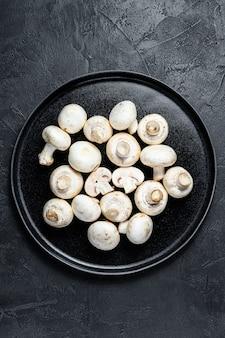 Fresh mushrooms champignon on a plate.