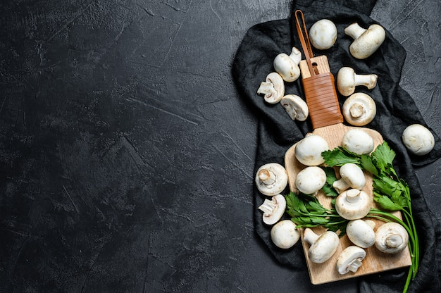 Fresh mushrooms champignon on a wooden cutting board. black wall. top view. space for text