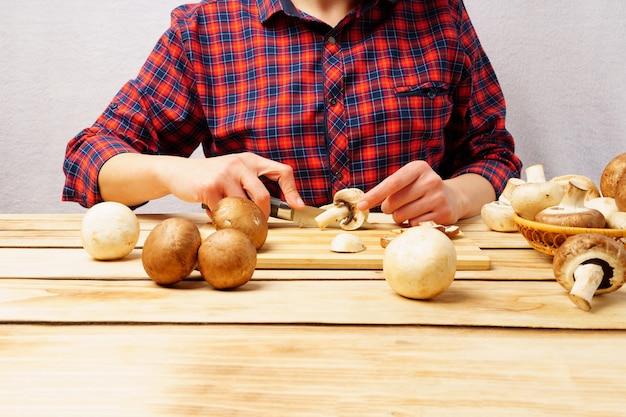 나무 보드에 신선한 버섯 champignons입니다. 소녀는 칼로 버섯을 자른다.