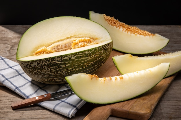 Fresh muskmelon with slices on wooden table