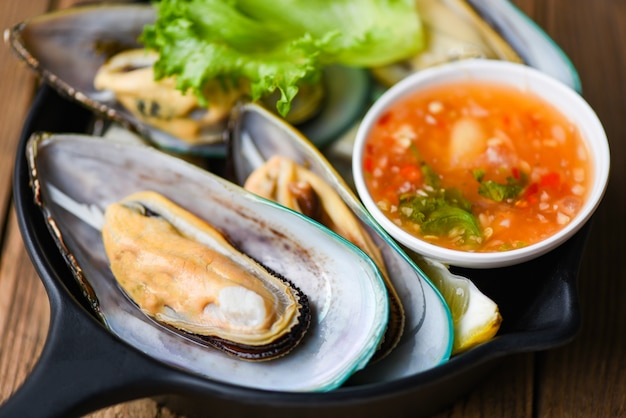 Fresh mussels on black bowl and seafood sauce