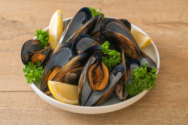 Fresh mussels with herbs in a bowl with lemon