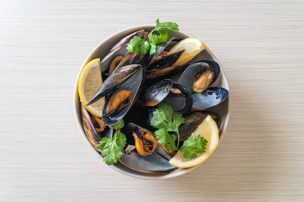 レモンとボウルにハーブと新鮮なムール貝