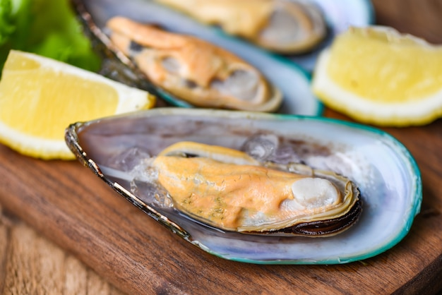 Fresh mussels on wooden and lemon shellfish steamed mussels /